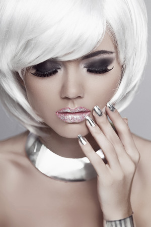 mulatto woman: Fashion blond girl with White Short Hair. Manicured nails. Mulatto woman. Eyes makeup. Beauty portrait. Jewelry accessories. Stock Photo