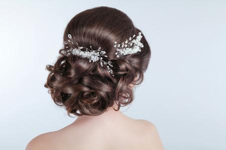 Peinado de boda de belleza. Novia. Chica morena con un estilo de pelo rizado con pasador.