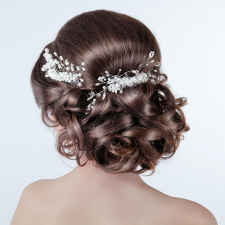 Brown hair styling. Brunette girl with curly hairstyle with barrette. Bride photo