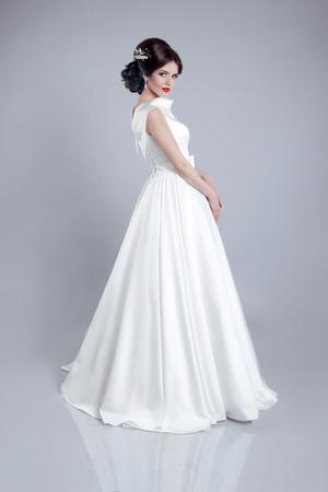 Fashionable bride model in wedding dress isolated on gray background. Studio photo