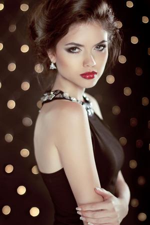Красивая брюнетка молодая женщина. Мода глэм девушка модель над боке