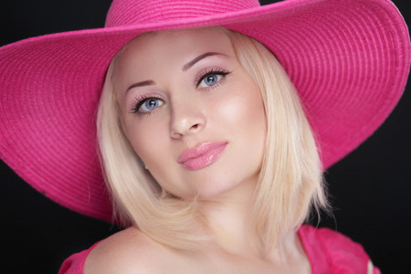 pink hat: Beauty fashion girl portrait. Blond female in pink hat isolated on black . Stock Photo