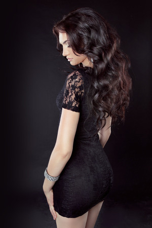 hair back: Beautiful Model brunette woman with long curly hair, in dress, isolated on black