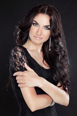 dark eyes: Beautiful brunette woman posing at studio isolated on black