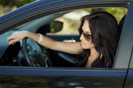 Brunette woman sitting in car, beautiful sexy female driver photo