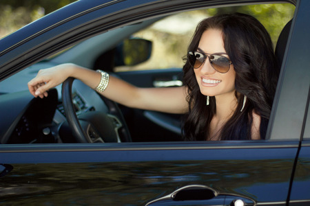 window shades: Smiling woman sitting in car, Happy girl driving automobile, outdoors summer portrait Stock Photo