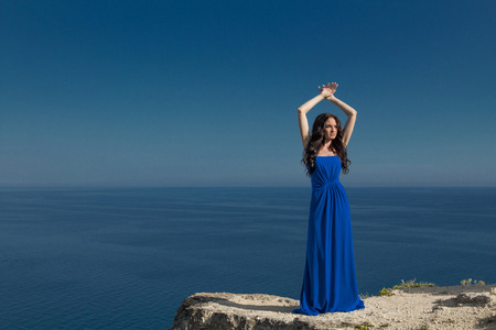 Summer portrait. Beautiful woman standing on a cliff over blue sky. Trendy model girl in long dress photo