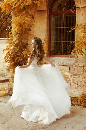 Beautiful bride woman in white wedding dress running at autumn park  Stock Photo