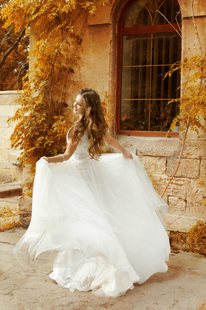 dress blowing in the wind: Beautiful bride woman in white wedding dress running at autumn park  Stock Photo