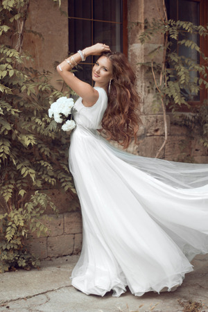 Beautiful brunette bride woman with long wavy hair in luxurious white wedding dress posing over wall at summer park photo