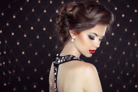 Элегантный брюнетка леди с макияж и прическа. Мода девушка модель над фоне боке огни Фото со стока
