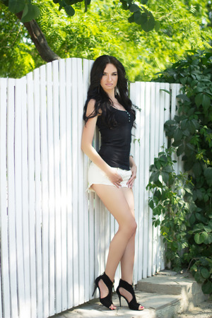Young brunette woman leaning against a white fence. Long wavy hair style photo