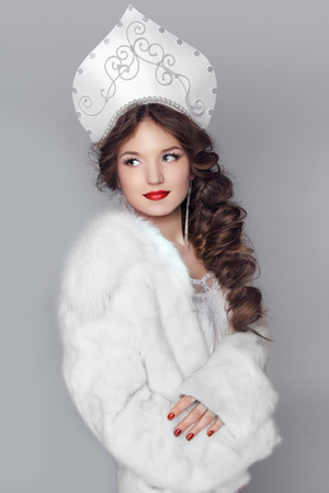 Fashion girl in fur coat and exclusive design clothes on manners old-Slavic. Close-up portrait. Russian woman model  photo