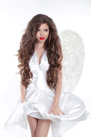 Long wavy Hair. Model Angel Girl in blowing dress with white wings  photo