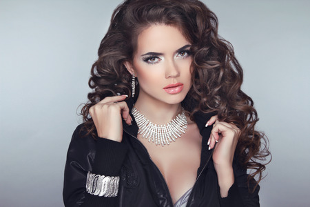 maquillaje de ojos: Modelo de la muchacha atractiva morena con largo cabello ondulado peinado, maquillaje y joyas de moda aisladas sobre fondo gris