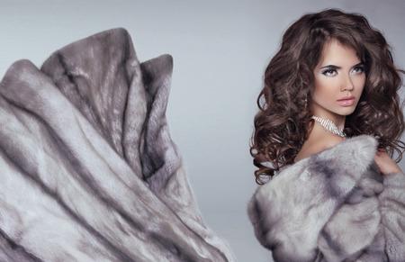 blue grey coat: Beautiful brunette woman in mink fur coat. Fashion Beauty girl model with long healthy wavy hair styling. Stock Photo