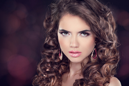 Beautiful brunette woman. Long wavy hair. Fashion earring. Professional makeup. photo