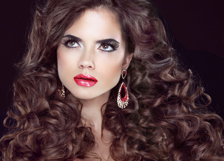 make up eyes: Beauty fashion girl. Wavy long hair. Brunette model with red lips, makeup and curly hairstyle.
