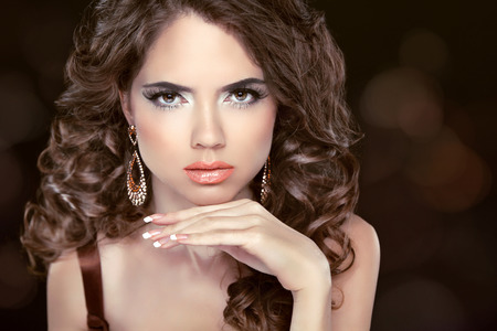 Beautiful fashion brunette woman model with wavy long hair and fashion earrings. Professional makeup. photo