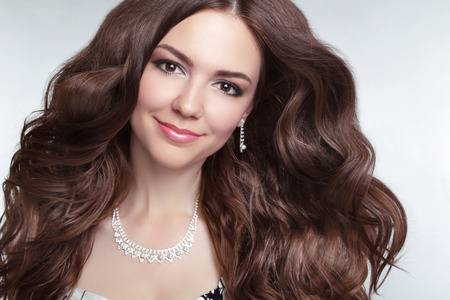 Attractive brunette young smiling woman Model Portrait. Long healthy Wavy hair. Professional makeup. Jewelry photo