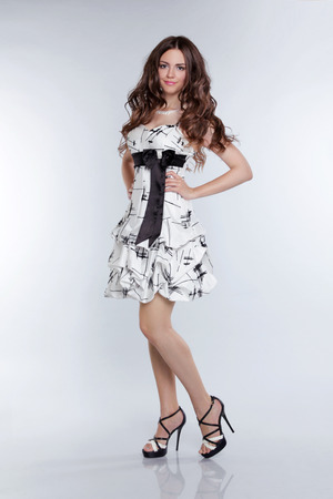 Portrait of a beautiful brunette posing in dress at the studio photo