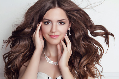 jewellery: Long blowing hair. Beautiful brunette girl model with makeup, fashion jewelry, wavy hairstyle.