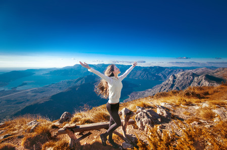 top of the world: Happy freedom woman with opened arms, on the top of a mountain, enjoying bliss travel holidays vacation outdoors. Stock Photo