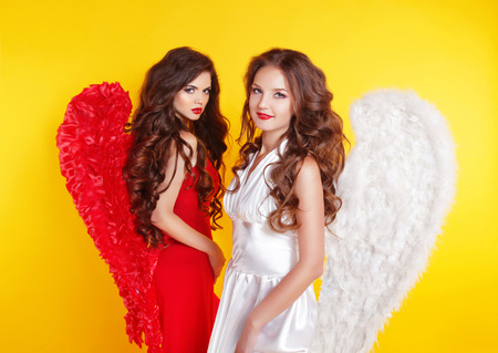 devil woman: Two Attractive Women wearing in angel costume with wings isolated on Yellow Background.