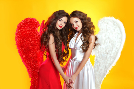 Beautiful Brunette Angel girls with angel's wings. Fashion women with long wavy hair wearing in red and white clothes. Stock Photo