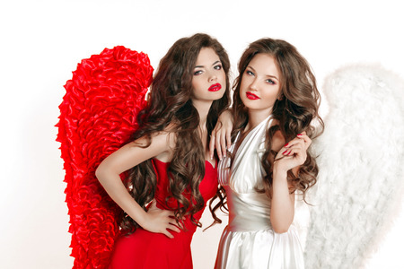 sisters sexy: Beautiful Angel girls with angels wings. Fashion women with long wavy hair wearing in red and white dress clothes. Isolated on white background