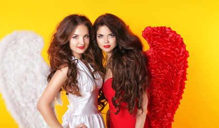 Glamorous fashion beautiful angel girls with angels wings. Valentine Day Women.  Isolated on yellow background. photo