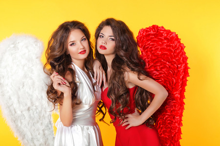 Glamorous fashion brunette angel girl with angels wings. Valentine Day Women.  Isolated on yellow background. photo