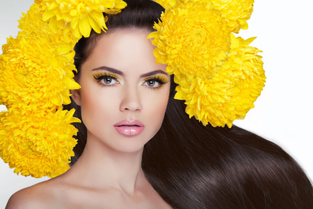 Beautiful girl with long shiny straight brown hair styling. Young attractive woman with flowers on head. Фото со стока