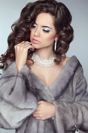 Beauty Fashion Model Woman in Mink Fur Coat. Winter Brunette Girl in Luxury clothes. Long wavy hair. Makeup. Jewelry. photo