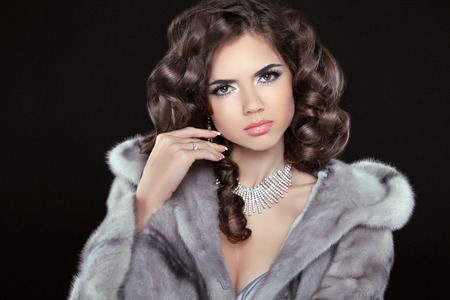 Fashion Beautiful girl with brown long wavy hair, Shine hairstyle with health. Makeup. Jewelry. Fashionable woman in mink fur coat. photo