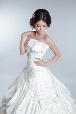 voluminous: Bridal makeup, hairstyle. Beautiful charming bride in wedding luxurious dress with voluminous skirt, studio photo Stock Photo