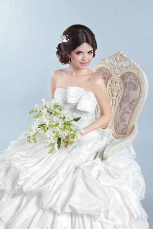 voluminous: Beautiful bride girl wearing in wedding dress with voluminous skirt posing on chair, studio photo