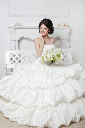 hair studio: Beautiful attractive bride in wedding luxurious dress with voluminous skirt posing in modern interior