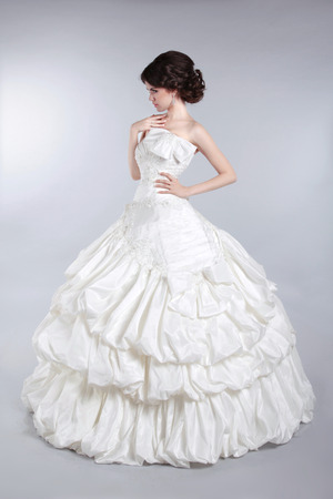 voluminous: Beautiful attractive bride model wearing in wedding dress with voluminous skirt, studio photo Stock Photo