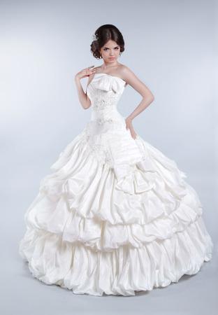 voluminous: Attractive bride model girl wearing in wedding dress with voluminous skirt, studio photo Stock Photo