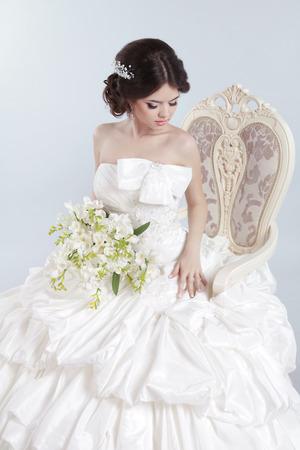 voluminous: Bride. Beautiful brunette woman wearing in modern wedding dress with voluminous skirt, posing on modern armchair, studio photo. Fashion girl model.