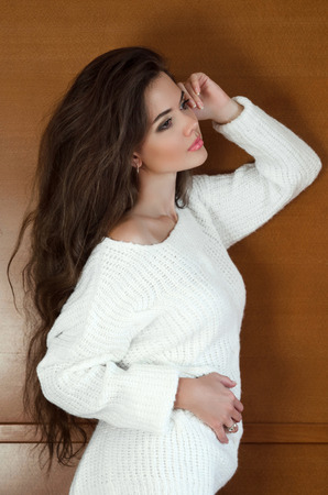 woman sweater: Beautiful brunette woman in white sweater with Healthy Long Wavy Hair