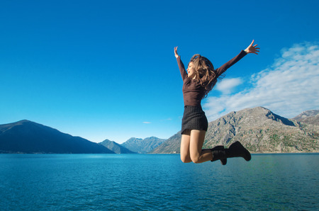 montenegro: Beautiful Jumping Girl enjoying nature with her opened arms over blue sky, mountains