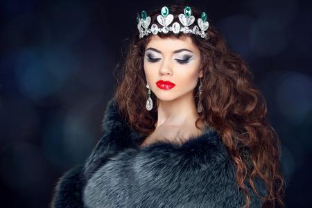 Beautiful brunette woman in mink fur coat. Jewelry. Fashion Beauty girl model with long healthy wavy hair styling. photo