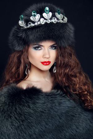 Beauty Fashion Model Girl in Fur Coat. Diamond jewelry. Beautiful Luxury Winter Woman in fur hat. photo