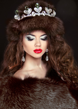 Beautiful brunette woman in mink fur coat. Jewelry. Fashion Beauty girl model with long healthy wavy hair styling. photo