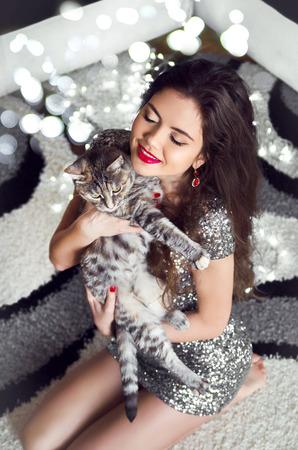 cola mujer: Mujer joven hermosa que abraza y sostiene el gato sobre Boker luces de Navidad de fondo.