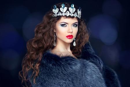 christmas crown: Mujer morena hermosa en abrigo de piel de vis�n. Joyer�a. Modelo de la chica de moda la belleza con el pelo ondulado largo estilo saludable. Foto de archivo