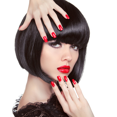 Beauty fashion brunette model portrait. Manicured nails. Red lips. Professional makeup. Bob hairstyle. Trendy girl isolated on white studio background.