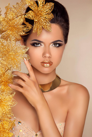fascinating: Beautiful Attractive Girl With Golden Flowers. Beauty Model Woman Face. Perfect Skin. Professional Make-up. Makeup. Stock Photo